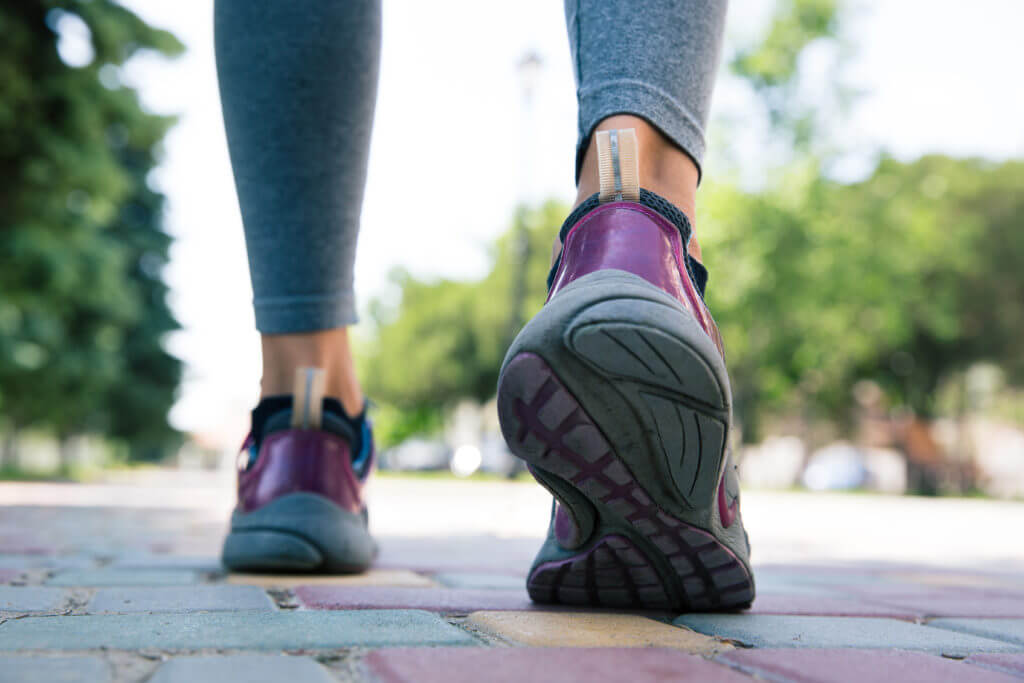 Footwear on female feet running on road outdoors